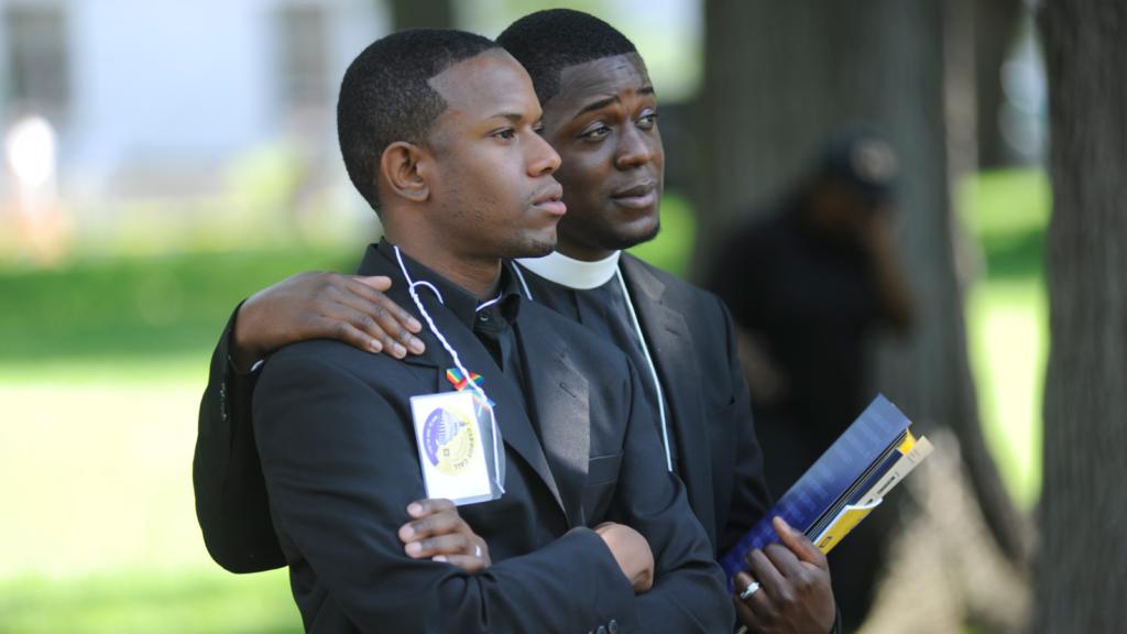 black pastor with arms around a black man