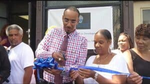 black man cutting blue ribbon in front of a store front
