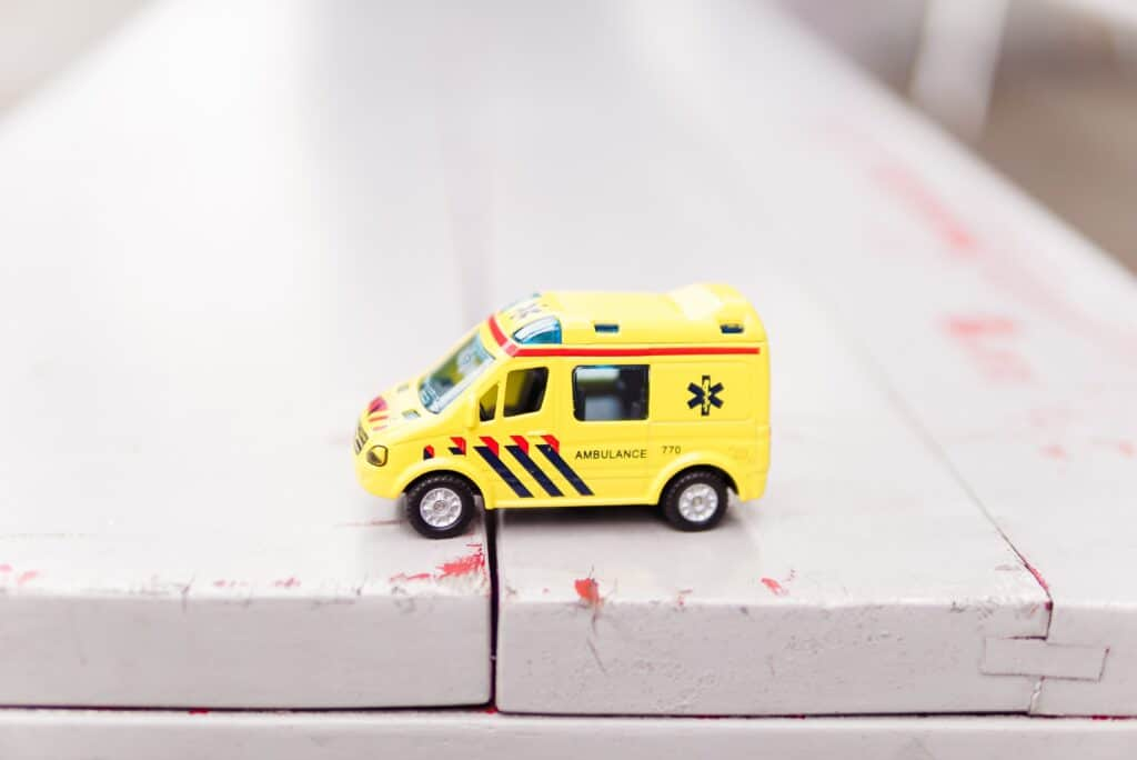 yellow toy ambulance truck on white surface