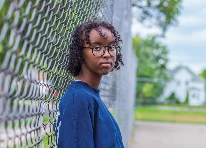 Isra HirsiII young black black leaning back on a chain link fence looking at the camera