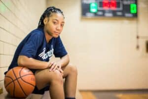 Mo'ne Davis sitting next to a basketball