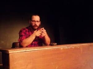 white man sitting at a desk on a theater stage