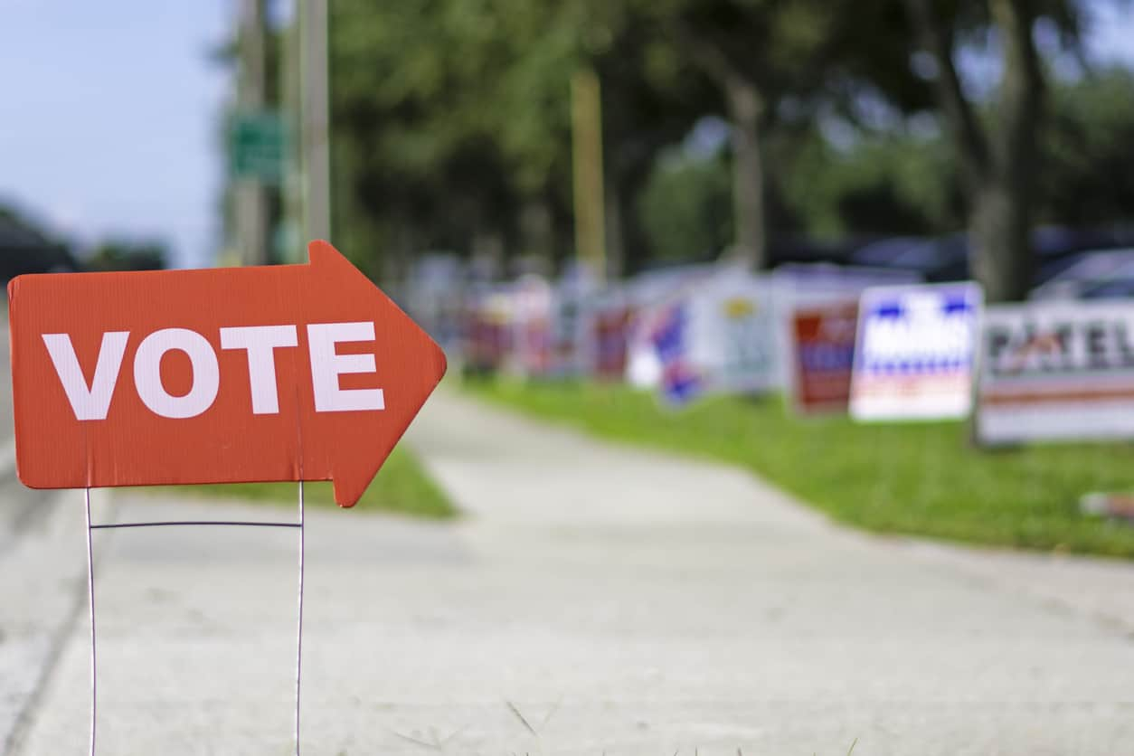 Sign directing voters to polling place with political signs in the background
