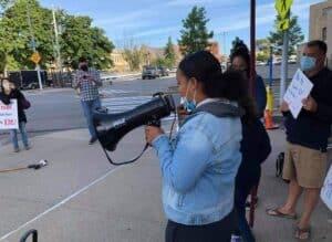 Youth girl teen activist with black bull horn on street