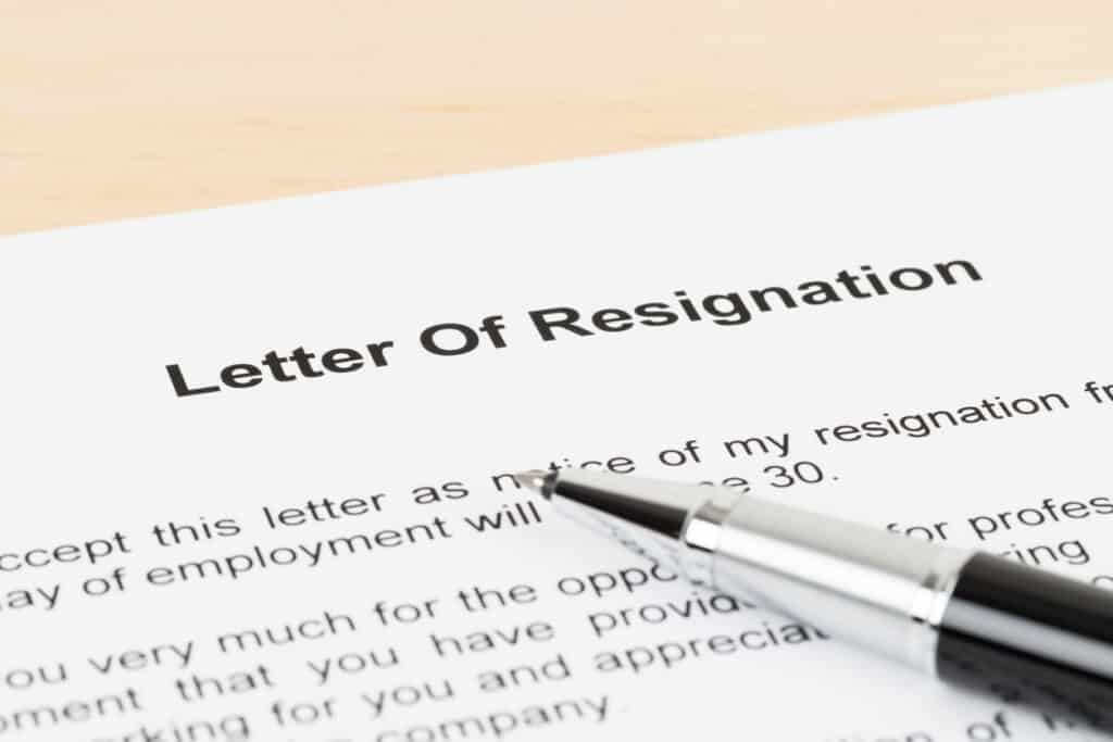 close up of letter of resignation with a pen