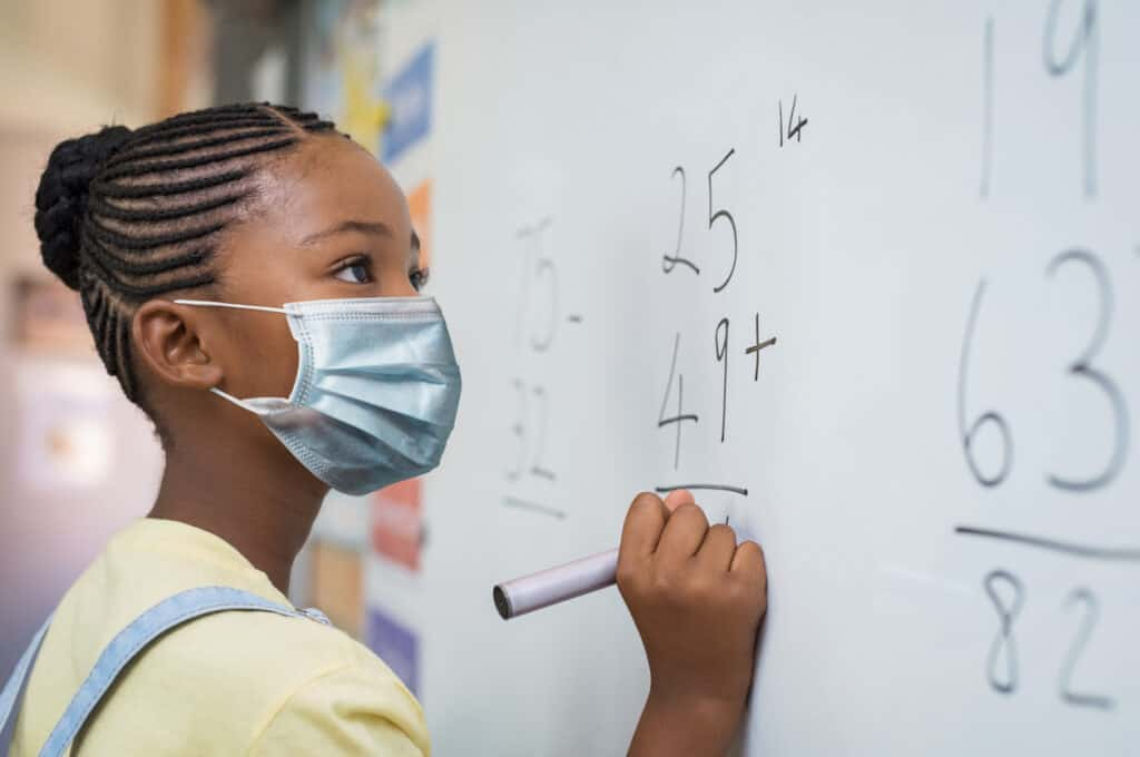 Portrait of african girl wearing face mask and writing solution of sums on white board at school. Black schoolgirl solving addition sum on white board during Covid-19 pandemic. School child thinking while doing mathematics problem and wearing surgical mask due to coronavirus.