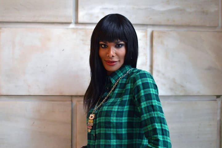 head shot of Black trans-woman with a green and black check shirt