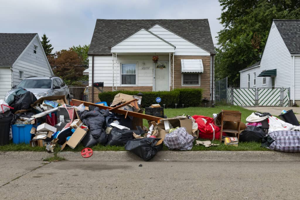 An evicted house at a suburban street with left belongings on the lawn